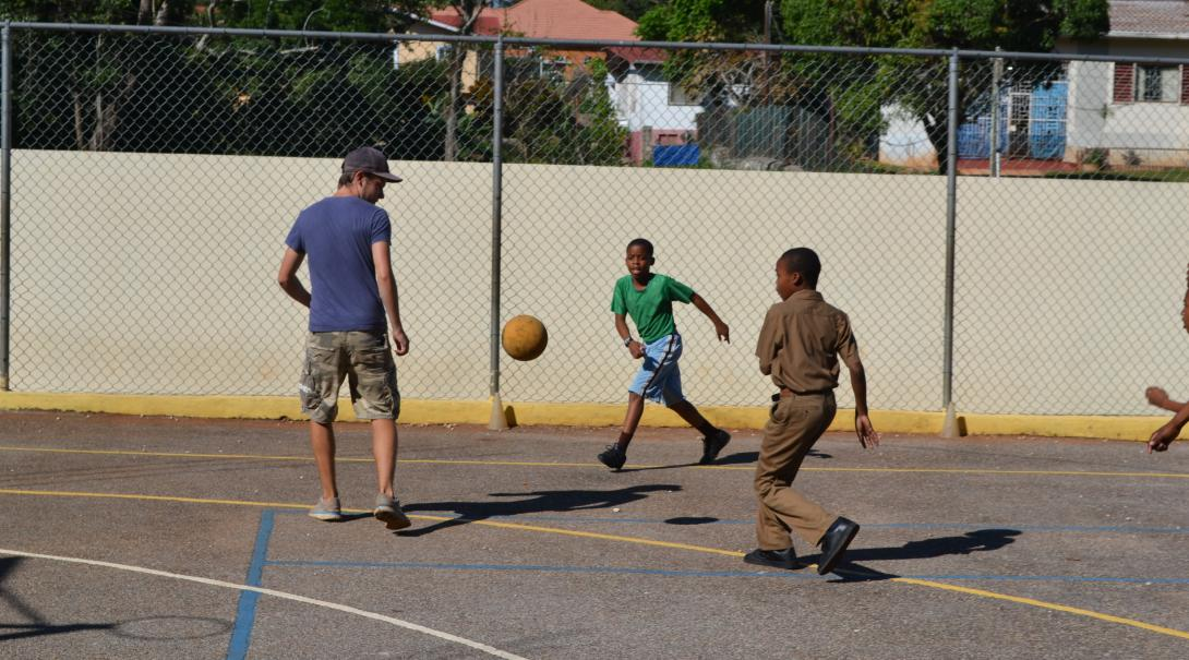A volunteer playing soccer with Jamaican kids on the courts while coaching them